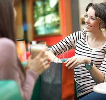 Stunning women after shopping talking with friend